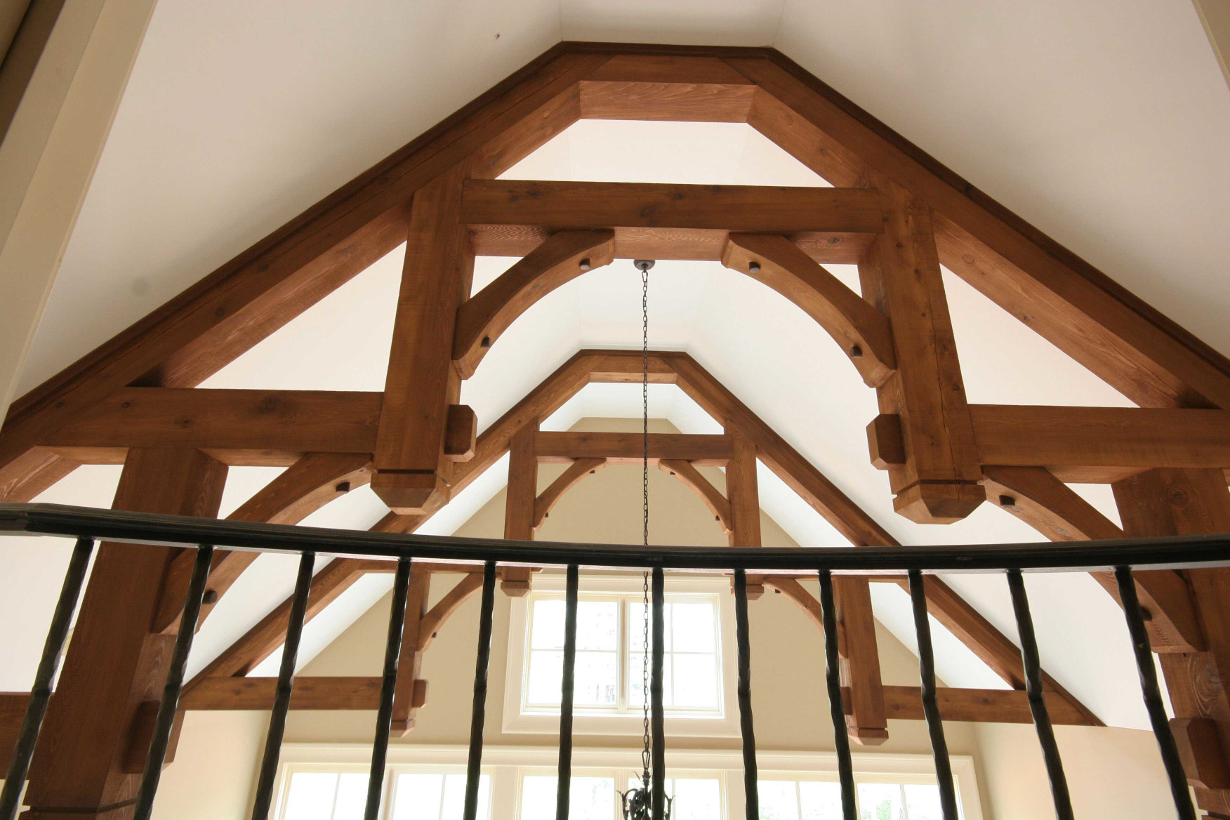 The wood braces and wood beams used creating these wood trusses are elegant features in the interior of this home