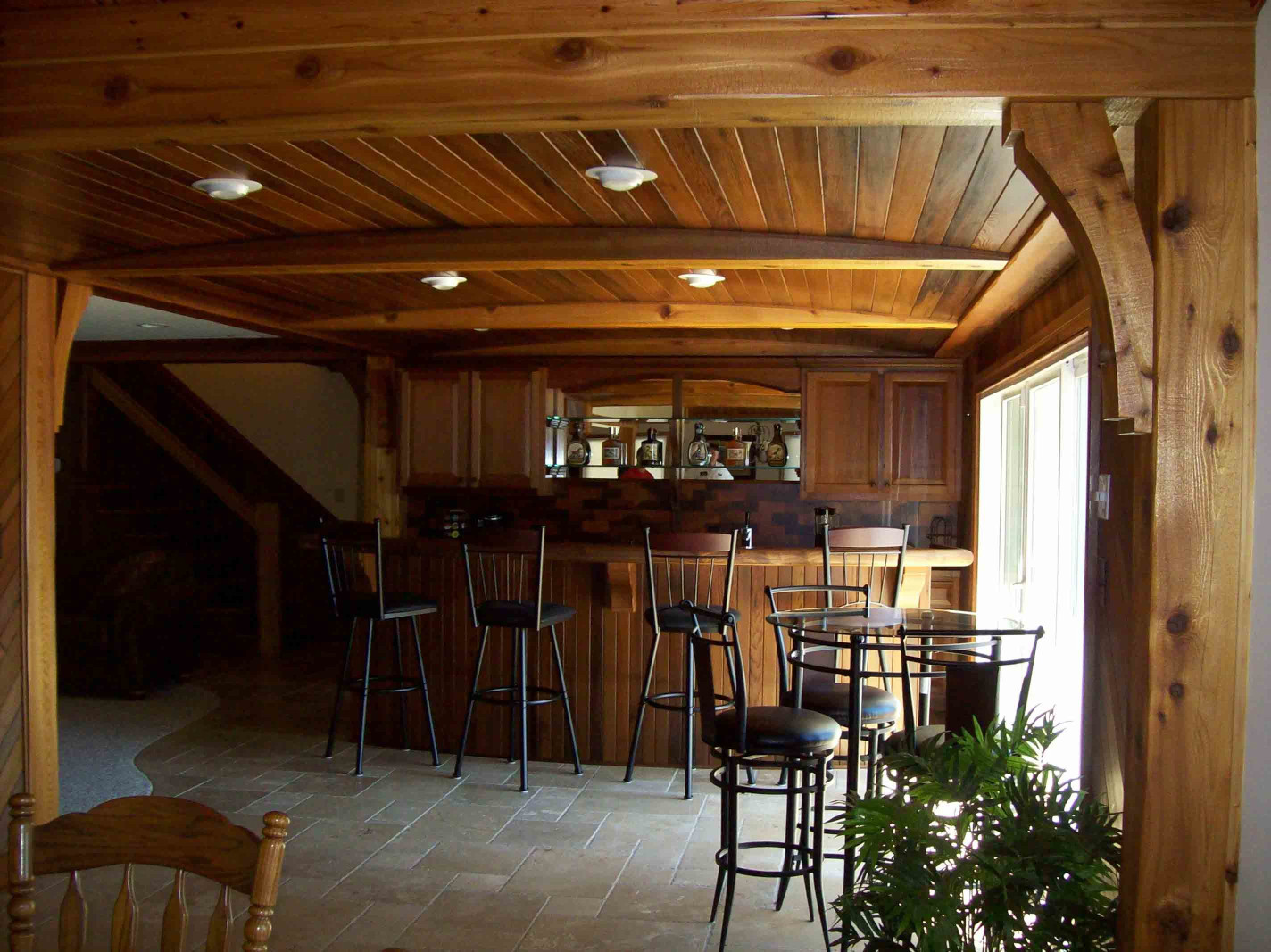 The custom wood beams, wood posts, wood braces, wood bar, and end grain backsplash, and cabinets in this home are completely unique.