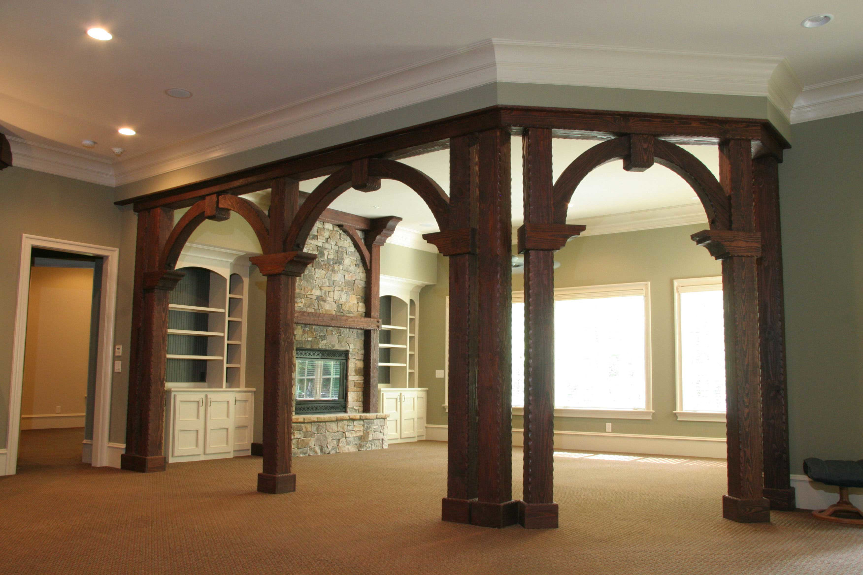 This custom designed interior entry includes wood posts, wood beams, wood beam ends, wood braces, and a wood mantel with legs.