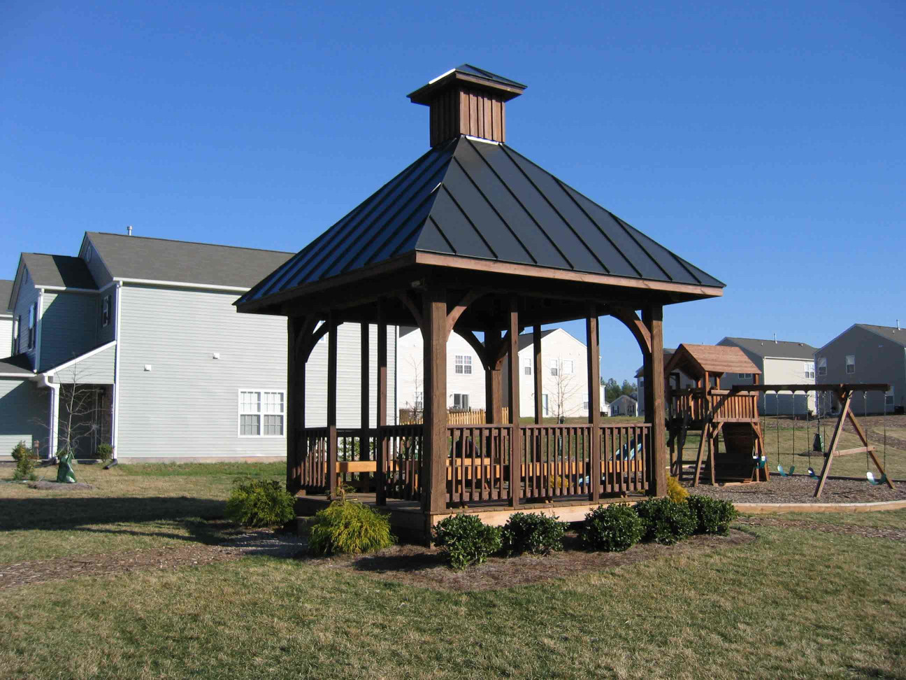 This Gazebo Kit with wood beams, wood braces, and wood raling looks great in this common area.