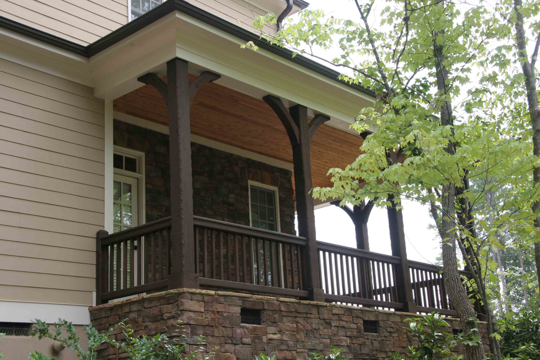 The wood braces and posts on this home add to the elegance of this wrap around porch.
