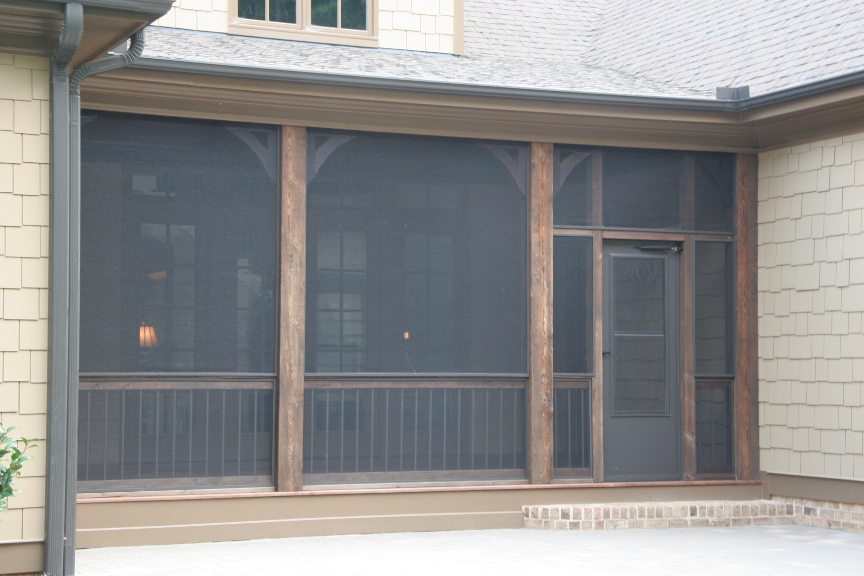 The wood posts and wood brackets and wood railing are a great addition to this screened porch
