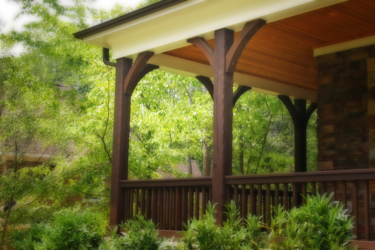 The wood braces, wood posts and wood railing on this porch coordinate nicely for a finished look.