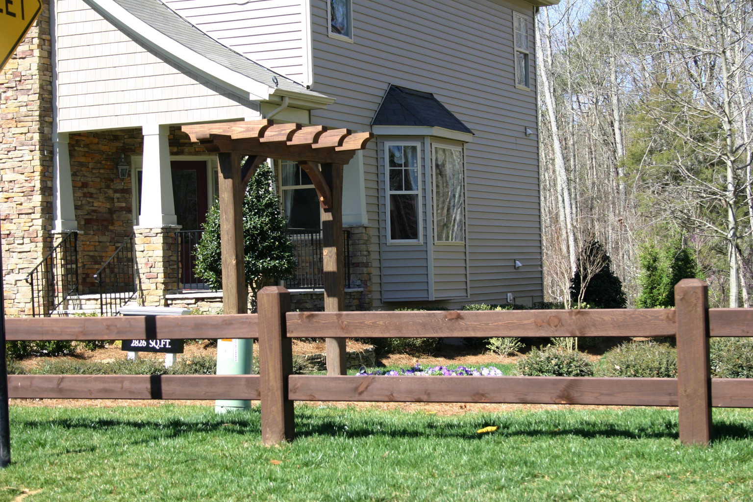 The wood posts and wood braces and  trellis look great in this front yard.