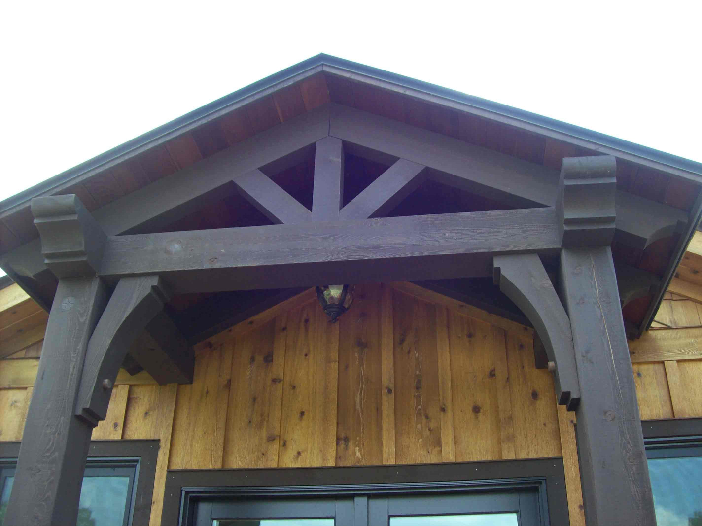 This wood gable bracket with wood posts and wood braces is a great way to add appeal to a home.