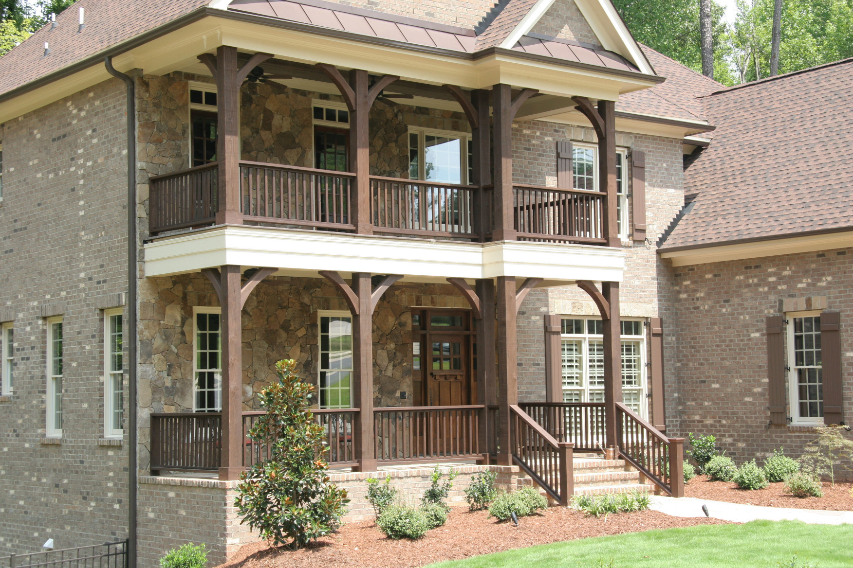 Our wood braces, posts and railing on this home create an old world feel on this two story front porch.