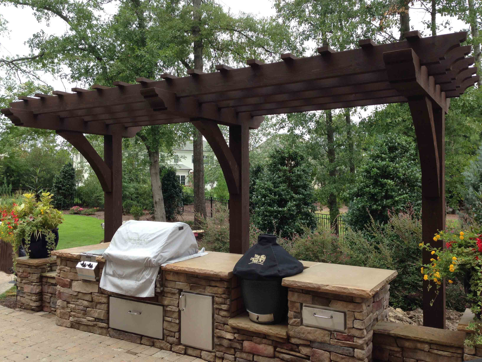 This wood arbor over this grill is a great way to add to this outdoor living space.