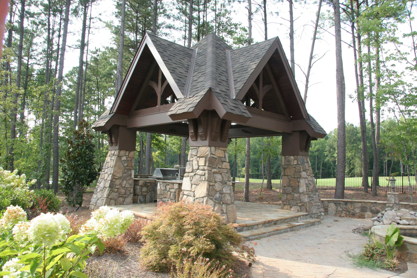 The wood brackets, gable trusses, and wood beams on this gazebo create a breathtaking outdoor living area.