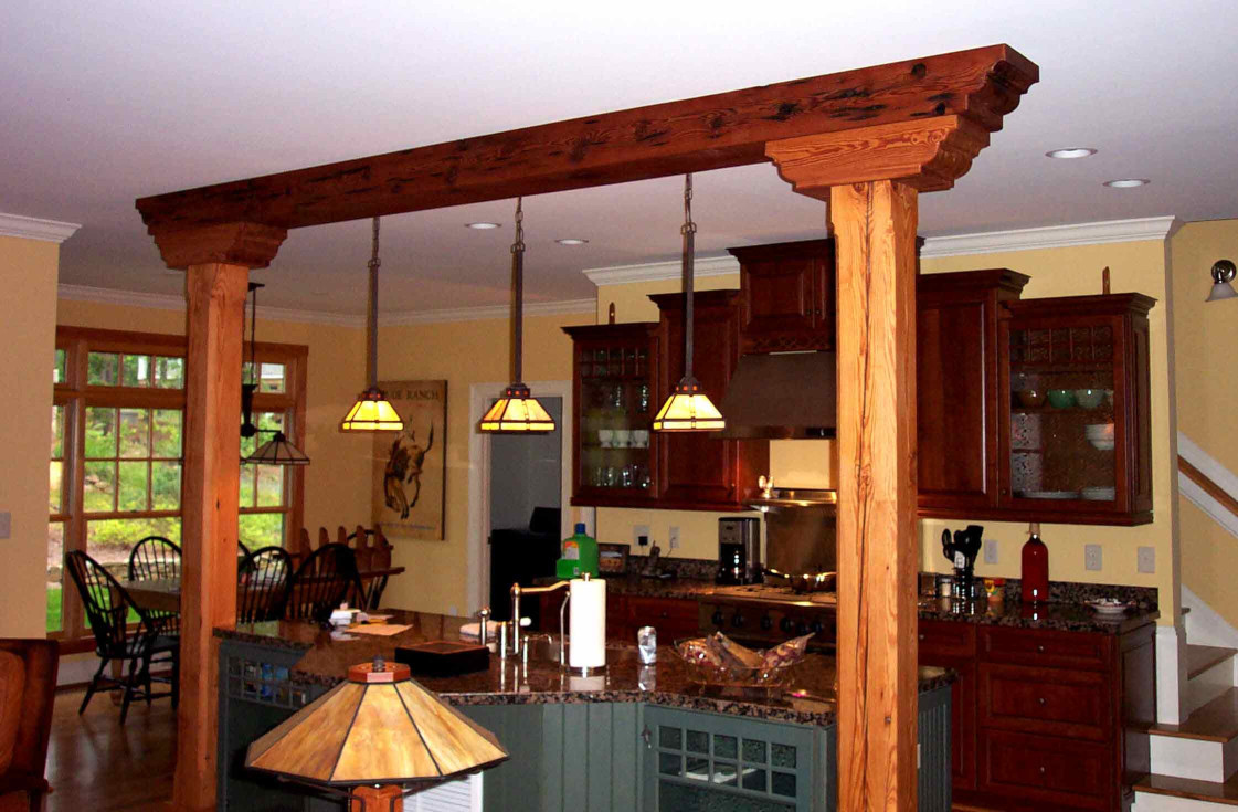 This wood beam, wood posts, and beam end combination define space between this great room and kitchen.