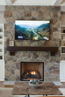 This wood mantle with corbel accents is the perfect complement to this stone fireplace.