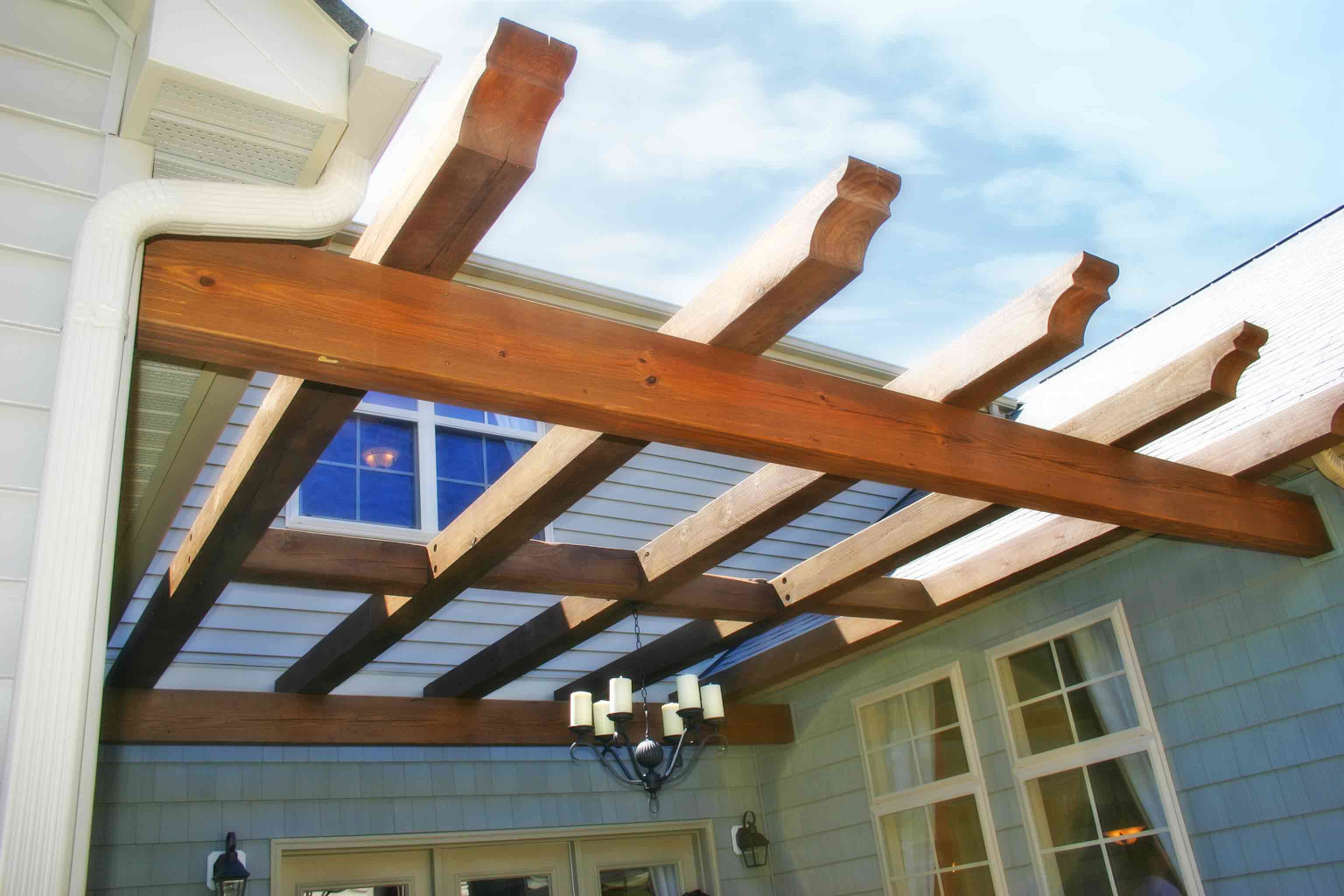 This wood pergola is a great way to add shade and appeal to this courtyard.