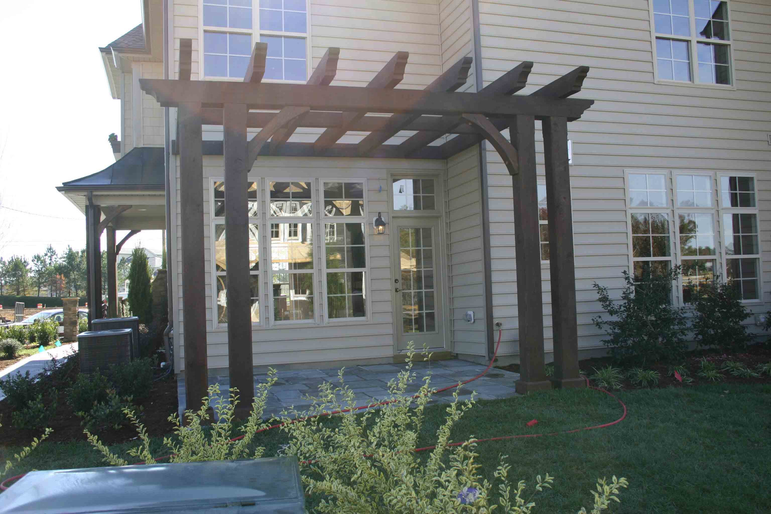 This wood pergola is a great  way to add to a side entry.
