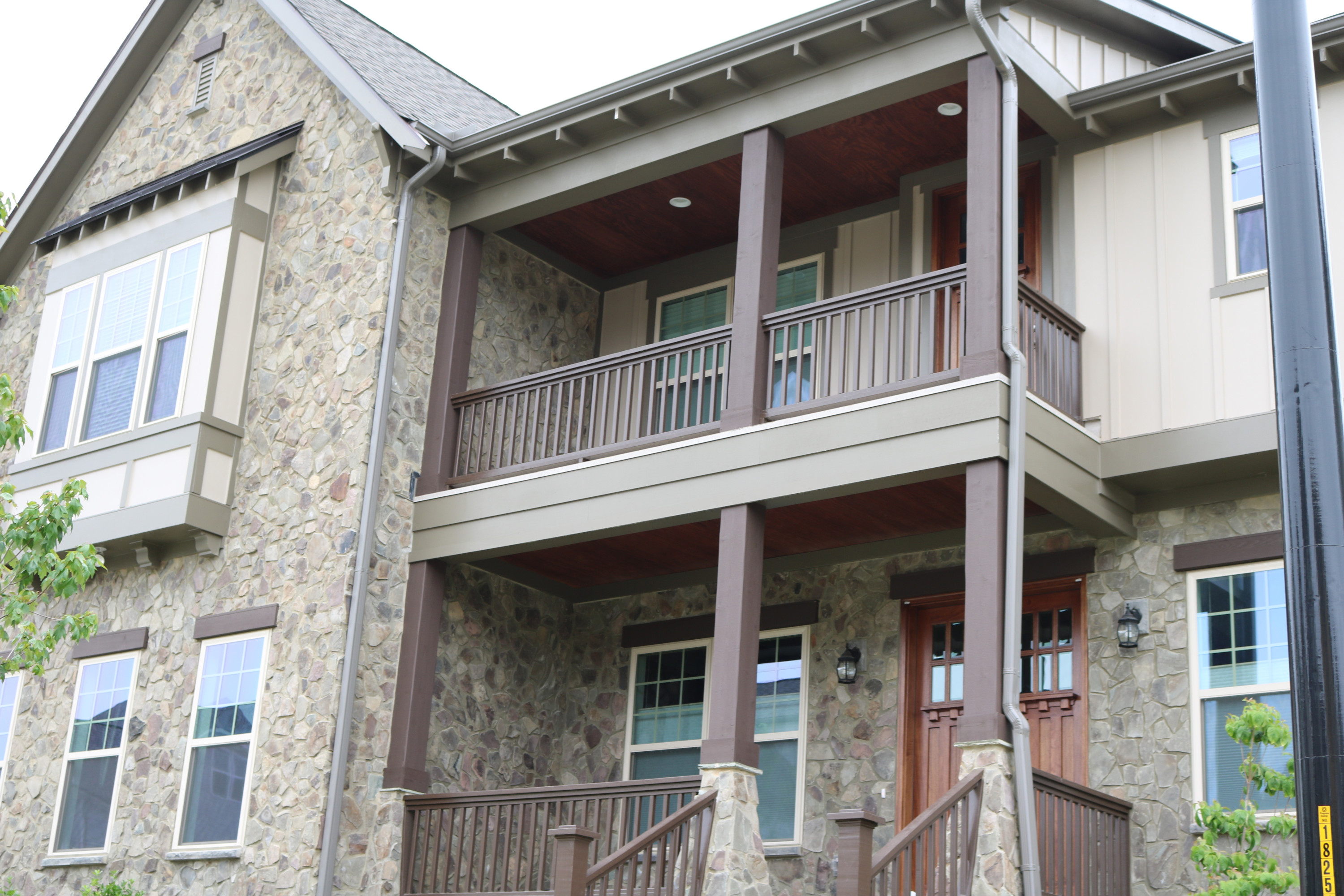 These wood post wraps and railings completel the 2 story porch on this home.