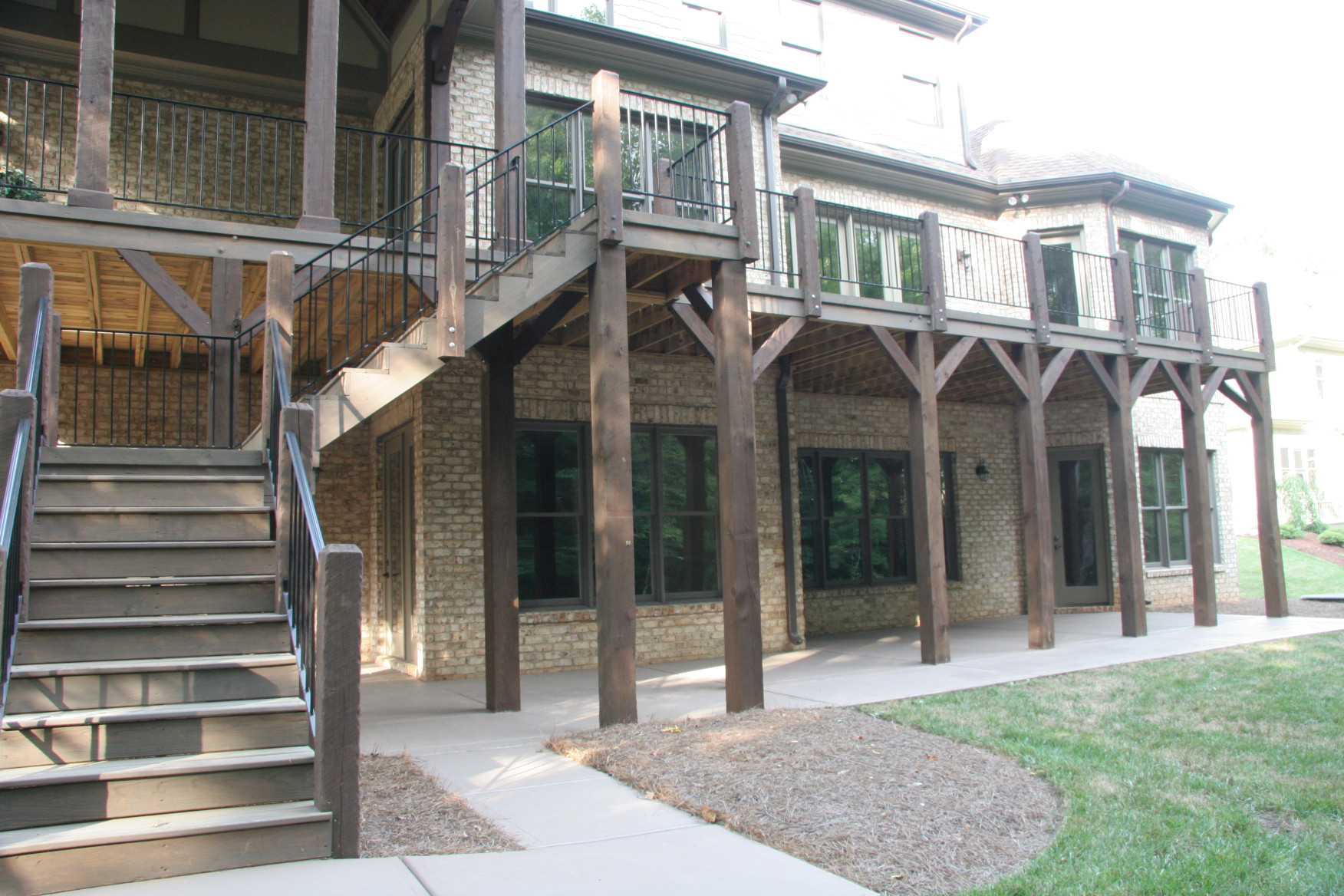 The wood posts and wood wood railing posts on this porch come together to create an Old World feel.