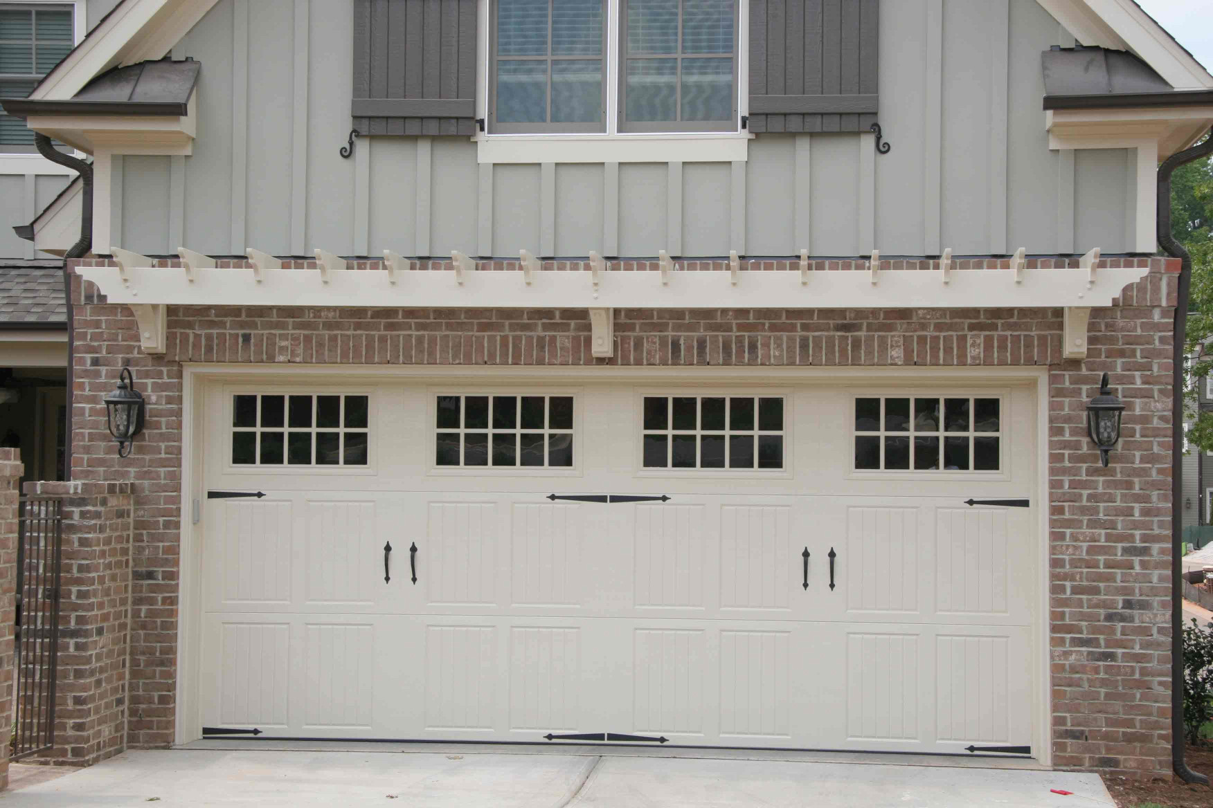 This wood trellis over a garage entry is an excellent addition to this home.